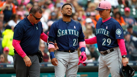 Seattle Mariners' Robinson Cano (22) grimaces while being attended to by trainer Rob Nodine, left, and manager Scott Servais (29) after being hit in the hand by a Detroit Tigers' Blaine Hardy pitch in the third inning of a baseball game in Detroit, Sunday, May 13, 2018. Cano left the game. (AP Photo/Paul Sancya)