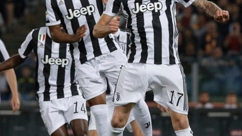 Juventus' Mario Mandzukic heads the ball next to teammate Alex Sandro, during a Serie A soccer match between Roma and Juventus, at the Rome Olympic stadium, Sunday, May 13, 2018. (AP Photo/Gregorio Borgia)