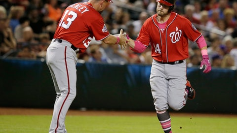 Washington Nationals Mark Raynolds (14) celebrates with Bob Henley after hitting a two run home run against the Arizona Diamondbacks in the eighth inning during a baseball game, Sunday, May 13, 2018, in Phoenix. (AP Photo/Rick Scuteri)