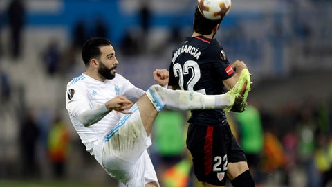 FILE - In this Thursday March 8, 2018 file photo, Marseille's Adil Rami, left, kicks the ball next to Bilbao's Raul Garcia during the Europa League round of 16, 1st leg soccer match between Marseille and Athletic Bilbao, at the Velodrome stadium, in Marseille, southern France. Marseille will play Atletico Madrid in the Europa League final on Wednesday May 16, 2018. Marseille now enjoys significant financial backing and the time is right to stop harping on about past glory and deliver another trophy. Atletico is bidding to win the Europa League for the third time this decade. (AP Photo/Claude Paris, File)