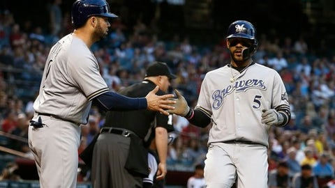Milwaukee Brewers' Jonathan Villar (5) and Manny Pina, left, celebrate their runs scored against the Arizona Diamondbacks during the second inning of a baseball game Monday, May 14, 2018, in Phoenix. (AP Photo/Ross D. Franklin)