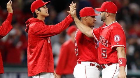 Los Angeles Angels starting pitcher Shohei Ohtani, left, of Japan, and Albert Pujols celebrate their team's 2-1 win against the Houston Astros in a baseball game, Monday, May 14, 2018, in Anaheim, Calif. (AP Photo/Jae C. Hong)