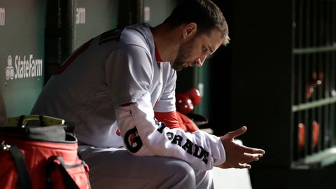 "FILe - In this April 17, 2018, file photo, St. Louis Cardinals starting pitcher Adam Wainwright looks down at his hand in the dugout during the third inning of the team's baseball game against the Chicago Cubs in Chicago. The Cardinals placed Wainwright back on the 10-day disabled list, Tuesday, May 15, 2018, after the right-hander struggled with velocity in his last start and said he needed ""to pause and get it right."" (AP Photo/Charles Rex Arbogast, File)"