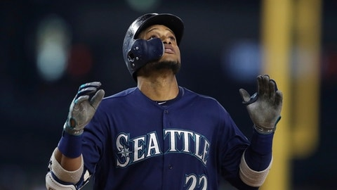 FILE - In this May 12, 2018, file photo, Seattle Mariners' Robinson Cano looks skyward as he crosses home plate after hitting a three-run home run during the fifth inning of the second baseball game of a doubleheader against the Detroit Tigers in Detroit. Cano has been suspended 80 games for violating baseball's joint drug agreement, the league announced Tuesday, May 15, 2018. (AP Photo/Carlos Osorio, File)