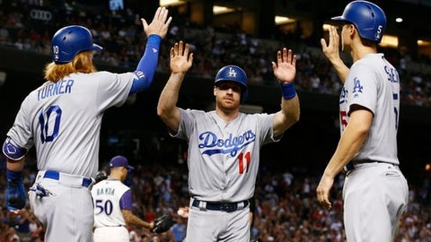Los Angeles Dodgers' Logan Forsythe (11) celebrates with Justin Turner (10) and Corey Seager, right, after all three scored against the Arizona Diamondbacks on a double by Enrique Hernandez during the first inning of a baseball game Thursday, Aug 10, 2017, in Phoenix. (AP Photo/Ross D. Franklin)
