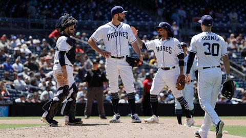 San Diego Padres starting pitcher Jordan Lyles, center, is greeted by teammates before leaving the baseball game against the Colorado Rockies during the eighth inning Tuesday, May 15, 2018, in San Diego. (AP Photo/Gregory Bull)