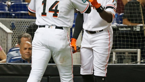 Miami Marlins' Martin Prado (14) is congratulated by Cameron Maybin after Prado scored during the first inning of a baseball game against the Los Angeles Dodgers on Tuesday, May 15, 2018, in Miami. (AP Photo/Wilfredo Lee)