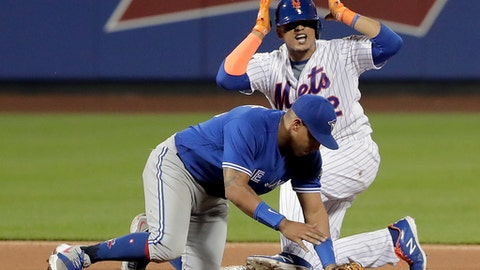 New York Mets' Juan Lagares motions to the dugout after advancing to second base following his single, ahead of the tag from Toronto Blue Jays second baseman Yangervis Solarte during the fourth inning of a baseball game, Tuesday, May 15, 2018, in New York. (AP Photo/Julie Jacobson)