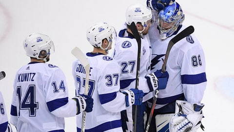 Tampa Bay Lightning's Andrei Vasilevskiy (88), of Russia, celebrates with Ryan McDonagh (27), Yanni Gourde (37) and Chris Kunitz (14) after Game 3 of the team's NHL Eastern Conference finals hockey playoff series against the Washington Capitals, Tuesday, May 15, 2018 in Washington. The Lightning won 4-2. (AP Photo/Nick Wass)
