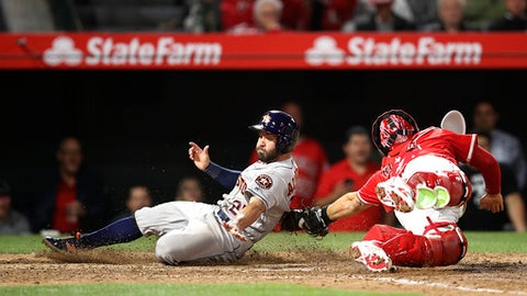Houston Astros' Jose Altuve, left, is tagged out by Los Angeles Angels catcher Rene Rivera during the eighth inning of a baseball game Tuesday, May 15, 2018, in Anaheim, Calif. (AP Photo/Jae C. Hong)
