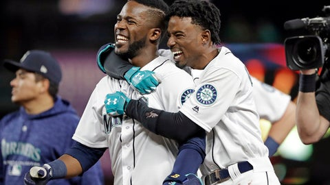 Seattle Mariners' Guillermo Heredia, left, is embraced by Dee Gordon after Heredia hit a one-run single to beat the Texas Rangers in the 11th inning of a baseball game Tuesday, May 15, 2018, in Seattle. The Mariners won 9-8. (AP Photo/Elaine Thompson)