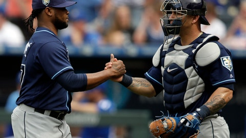 Tampa Bay Rays relief pitcher Alex Colome, left, is congratulated by catcher Wilson Ramos, right, following a baseball game against the Kansas City Royals at Kauffman Stadium in Kansas City, Mo., Wednesday, May 16, 2018. The Rays defeated the Royals 5-3. (AP Photo/Orlin Wagner)