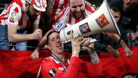 Surrounded by fans Atletico's Fernando Torres celebrates the 3-0 win of his team after the Europa League Final soccer match between Marseille and Atletico Madrid at the Stade de Lyon in Decines, outside Lyon, France, Wednesday, May 16, 2018. (AP Photo/Thibault Camus)