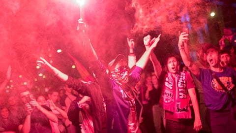 Atletico Madrid supporters light flares as they celebrate their team's Europa League tittle in Madrid, Wednesday, May 16, 2018. Atletico defeated Marseille 3-0 in the final and clinches its third Europa League title. (AP Photo/Francisco Seco)