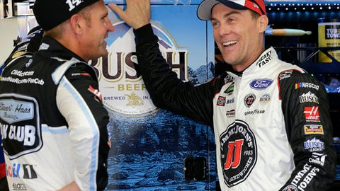 Kevin Harvick, right, talks with teammate Clint Bowyer during practice for Saturday's NASCAR Cup Series All Star auto race at Charlotte Motor Speedway, Friday, May 18, 2018 in Concord, N.C. (AP Photo/Terry Renna)