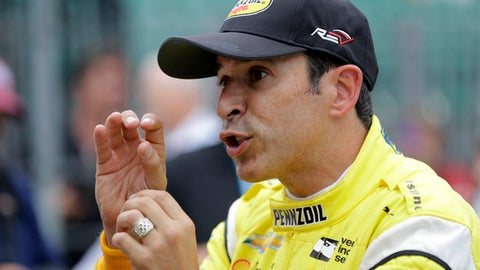 Helio Castroneves, of Brazil, talks with a crew member during a practice session for the IndyCar Indianapolis 500 auto race at Indianapolis Motor Speedway in Indianapolis, Friday, May 18, 2018. (AP Photo/Darron Cummings)