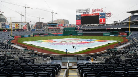A tarp covers the infield at Nationals Park in Washington after it was announced that the baseball game between the Los Angeles Dodgers and the Washington Nationals had been postponed due to inclement weather, Friday, May 18, 2018. The game will be made up as part of a split doubleheader Saturday. (AP Photo/Pablo Martinez Monsivais)