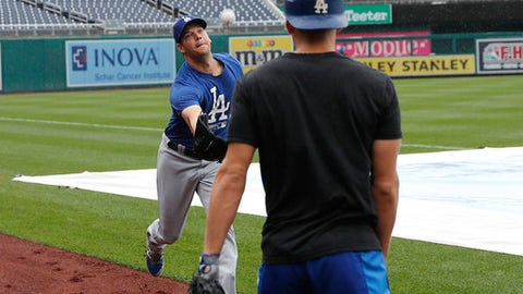 Los Angeles Dodgers starting pitcher Rich Hill, left, runs to catch a ball tossed to him by catcher Austin Barnes, right, as they head back to the dugout at Nationals Park in Washington after it was announced that baseball game against the Washington Nationals had been postponed due to inclement weather, Friday, May 18, 2018. The game will be made up as part of a split doubleheader Saturday. (AP Photo/Pablo Martinez Monsivais)