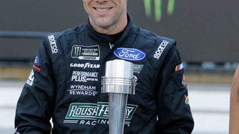 Matt Kenseth holds the trophy after winning the pole position for Saturday's NASCAR All-Star auto race at Charlotte Motor Speedway, Friday, May 18, 2018 in Concord, N.C. (AP Photo/Terry Renna)