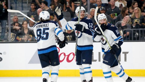 Winnipeg Jets' Mathieu Perreault, Jack Roslovic and Bryan Little, from left, celebrate after defenseman Tyler Myers's goal against the Vegas Golden Knights during the third period of Game 4 of the NHL Western Conference finals hockey playoff series Friday, May 18, 2018, in Las Vegas. (AP Photo/John Locher)