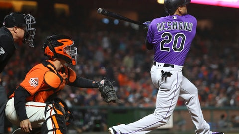 Colorado Rockies' Ian Desmond (20) swings for an RBI double off San Francisco Giants' Derek Holland during the sixth inning of a baseball game Friday, May 18, 2018, in San Francisco. (AP Photo/Ben Margot)