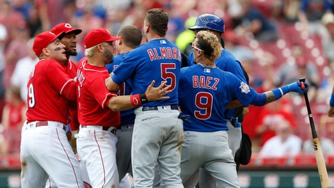 Chicago Cubs' Javier Baez, right, has a few words for Cincinnati Reds relief pitcher Amir Garrett, second from left, after striking out during the seventh inning in the first baseball game of a doubleheader, Saturday, May 19, 2018, in Cincinnati. (AP Photo/Gary Landers)