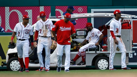 Washington Nationals second baseman Wilmer Difo, left, shortstop Trea Turner, manager Dave Martinez, and center fielder Michael Taylor, right, walk away as left fielder Howie Kendrick is taken away on the cart after an injury in the eighth inning of the first baseball game of a doubleheader against the Los Angeles Dodgers at Nationals Park, Saturday, May 19, 2018, in Washington. The Dodgers won the first game 4-1. (AP Photo/Alex Brandon)