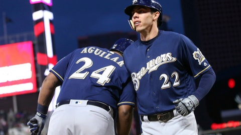 Milwaukee Brewers' Christian Yelich gets a celebratory bump from Jesus Aguilar, left, after his solo home run off Minnesota Twins pitcher Addison Reed duirng the eighth inning of a baseball game Saturday, May 19, 2018, in Minneapolis. The Brewers won 5-4. (AP Photo/Jim Mone)