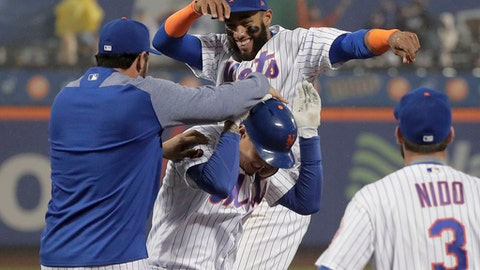 New York Mets' Wilmer Flores, center, is mobbed by teammates after driving in the winning run against the Arizona Diamondbacks on a sacrifice fly to left field during the ninth inning of a baseball game, Saturday, May 19, 2018, in New York. (AP Photo/Julie Jacobson)