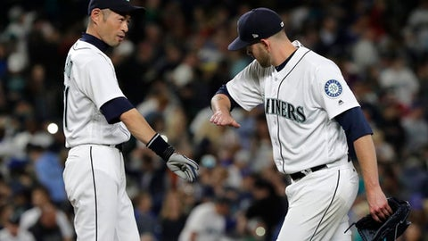 Ichiro Suzuki, left, Seattle Mariners special assistant to the chairman, greets starting pitcher James Paxton, right, Saturday, May 19, 2018, in Seattle after Paxton pitched a three-hitter against the Detroit Tigers in a baseball game with the Mariners won  7-2. (AP Photo/Ted S. Warren)