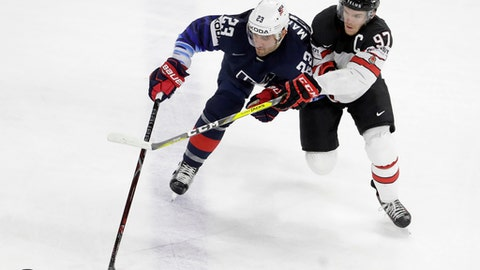 Alec Martinez of the United States, left, challenges for the puck with Canada's Connor McDavid during the Ice Hockey World Championships bronze medal match between Canada and the United States at the Royal arena in Copenhagen, Denmark, Sunday, May 20, 2018. (AP Photo/Petr David Josek)