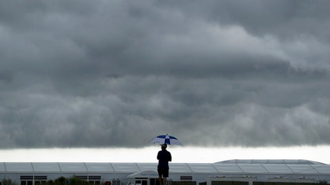 A lone fan stands along the course using an umbrella to shield himself from the rain during the rain-suspended final round of the AT&T Byron Nelson golf tournament, Sunday, May 20, 2018, in Dallas, Texas. (AP Photo/Eric Gay)