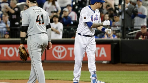 New York Mets' Wilmer Flores, right, gestures to teammates after hitting a RBI single as Miami Marlins first baseman Justin Bour, left, walks away during the seventh inning of a baseball game Monday, May 21, 2018, in New York. (AP Photo/Frank Franklin II)