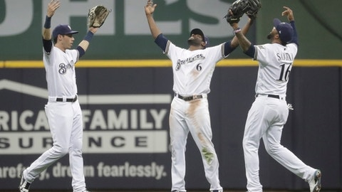 Milwaukee Brewers' Christian Yelich, Lorenzo Cain (6) and Domingo Santana (16) celebrate after a baseball game against the Arizona Diamondbacks Tuesday, May 22, 2018, in Milwaukee. The Brewers won 1-0. (AP Photo/Morry Gash)