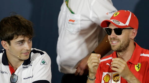Ferrari driver Sebastian Vettel of Germany, right, is flanked by Sauber driver Charles Leclerc of Monaco during a news conference, at the Monaco racetrack, in Monaco, Wednesday, May 23, 2018. The Formula one race will be held on Sunday. (AP Photo/Claude Paris)