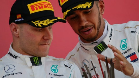 FILE - In this Sunday, May 13, 2018 file photo, Mercedes driver Lewis Hamilton of Britain, right, winner, celebrates on the podium with his teammate Mercedes driver Valtteri Bottas of Finland, second place, after the Spanish Formula One Grand Prix at the Barcelona Catalunya racetrack in Montmelo, Spain. Valtteri Bottas is urging his Mercedes teammate Lewis Hamilton to sign a new contract, even though he is own future is uncertain. Bottas needs to convince Mercedes to give him a new deal for 2019. (AP Photo/Emilio Morenatti, File)