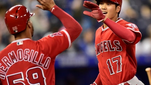 Los Angeles Angels' Shohei Ohtani celebrates with Michael Hermosillo as he scores against the Toronto Blue Jays on a single by Andrelton Simmons during the ninth inning of a baseball game in Toronto on Wednesday, May 23, 2018. (Frank Gunn/The Canadian Press via AP)