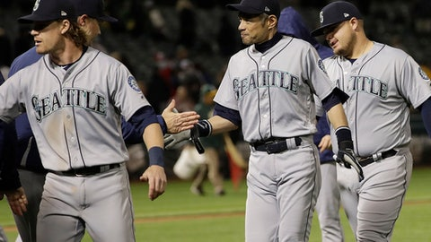 Seattle Mariners special assistant Ichiro Suzuki, center, celebrates with players after the Mariners beat the Oakland Athletics 1-0 in a baseball game in Oakland, Calif., Wednesday, May 23, 2018. (AP Photo/Jeff Chiu)