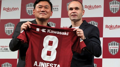 Former Barcelona player Andres Iniesta, right, holds his new uniform with Hiroshi Mikitani, left, owner of Vissel Kobe, during a press conference to join Japan's Vissel Kobe in Tokyo Thursday, May 24, 2018. Iniesta was introduced as the newest member of Japanese club Vissel Kobe on Thursday. (AP Photo/Eugene Hoshiko)