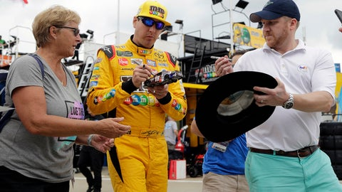 Kyle Busch, center, signs autographs before practice for the NASCAR Cup series auto race at Charlotte Motor Speedway in Charlotte, N.C., Thursday, May 24, 2018. (AP Photo/Chuck Burton)
