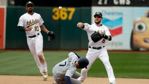 Oakland Athletics second baseman Jed Lowrie, right, completes a double play over Seattle Mariners' Andrew Romine (7) after a ground ball from David Freitas during the seventh inning of a baseball game Thursday, May 24, 2018, in Oakland, Calif. (AP Photo/Marcio Jose Sanchez)