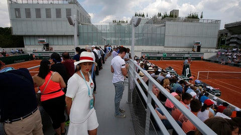 A hostess waits at the Roland Garros stadium in Paris, Friday, May 25, 2018. The French Open tennis tournament starts Sunday. (AP Photo/Michel Euler)