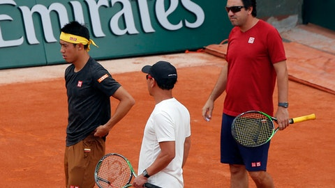 Japan's Kei Nishikori, left, trains with coaches Michael Chang, of the U.S, center, and Argentina's Dante Bottini at the Roland Garros stadium in Paris, Friday, May 25, 2018. The French Open tennis tournament starts Sunday. (AP Photo/Michel Euler)