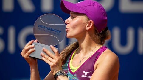 Sweden's  Johanna Larsson kisses the trophy after winning the women's WTA final in Nuremberg, Geermany, Saturday,May 26, 2018. (Daniel Karmann/dpa via AP)