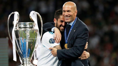Real Madrid's Isco hugs coach Zinedine Zidane, right, after winning the Champions League Final soccer match between Real Madrid and Liverpool at the Olimpiyskiy Stadium in Kiev, Ukraine, Saturday, May 26, 2018. (AP Photo/Pavel Golovkin)
