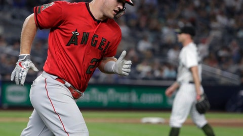 Los Angeles Angels' Mike Trout, left, runs after hitting a home run off New York Yankees starting pitcher Sonny Gray, right, during the fourth inning of a baseball game Saturday, May 26, 2018, in New York. (AP Photo/Julio Cortez)