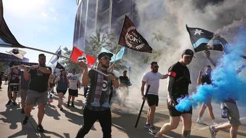 Minnesota United fans carrying smoke bombs parade into TCF Bank Stadium for the team's MLS soccer match against the Montreal Impact on Saturday, May 26, 2018, in Minneapolis. (Anthony Souffle/Star Tribune via AP)