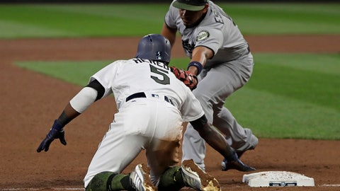 Seattle Mariners' Guillermo Heredia (5) is tagged out by Minnesota Twins third baseman Eduardo Escobar, right, after Heredia tried to steal third during the sixth inning of a baseball game Saturday, May 26, 2018, in Seattle. (AP Photo/Ted S. Warren)