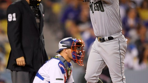 San Diego Padres' Christian Villanueva, right, claps as he scores after hitting a solo home run while Los Angeles Dodgers catcher Yasmani Grandal, center, and home plate umpire Brian Knight wait during the eighth inning of a baseball game Saturday, May 26, 2018, in Los Angeles. (AP Photo/Mark J. Terrill)