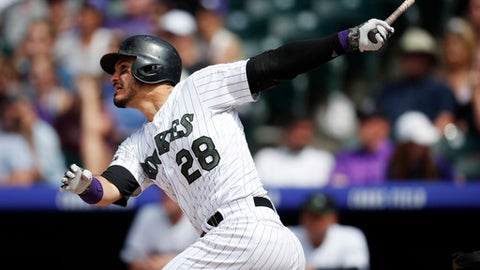 Colorado Rockies' Nolan Arenado follows the flight of his two-run home run off Cincinnati Reds relief pitcher Tanner Rainey in the sixth inning of a baseball game Sunday, May 27, 2018, in Denver. (AP Photo/David Zalubowski)